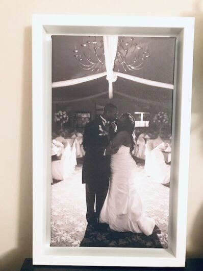 Wedding photo of couple kissing under a lights in an empty room
