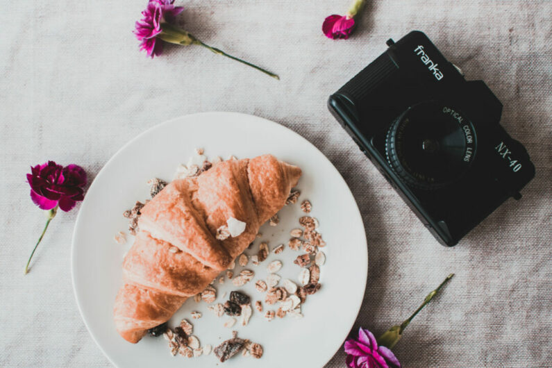 Black dslr camera with croissant in a plate